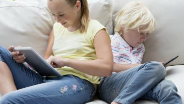 Brother and sister using digital tablets on outdoor sofa